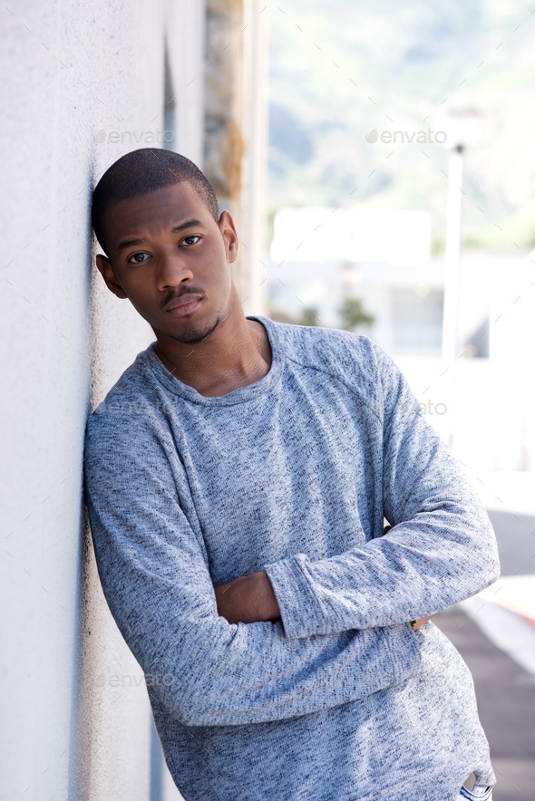 Portrait of young black man leaning against wall - Stock Photo - Images