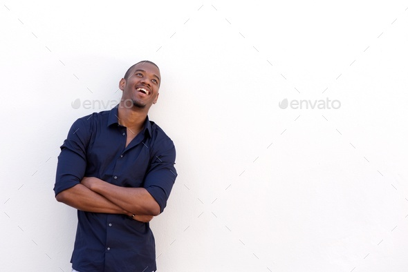 young black man laughing with arms crossed against white wall - Stock Photo - Images