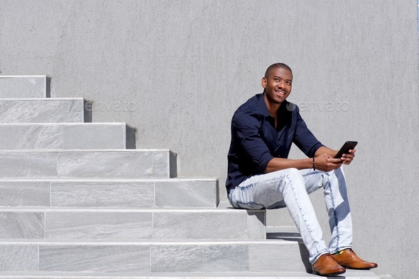 cool young black guy sitting on steps using digital tablet - Stock Photo - Images