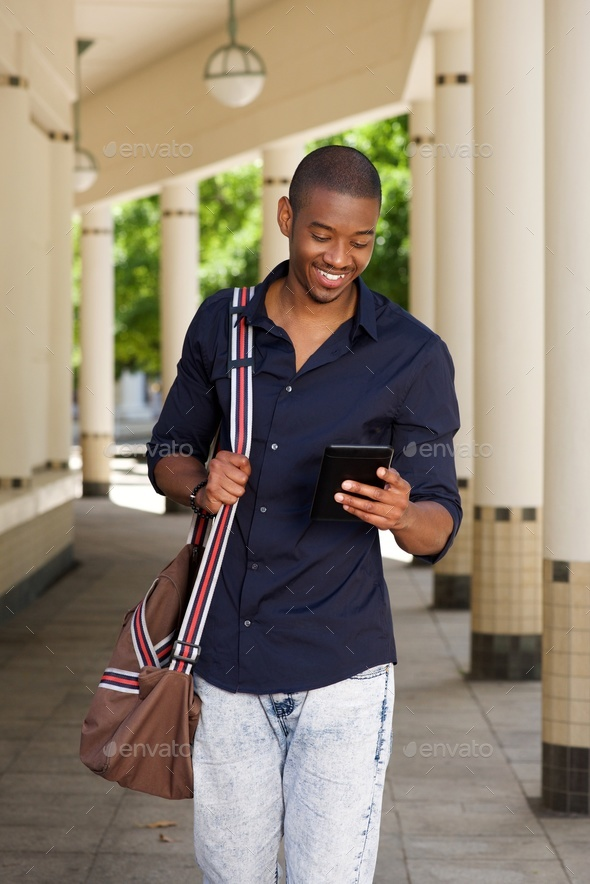 cool young black guy walking outside with mobile phone and bag - Stock Photo - Images