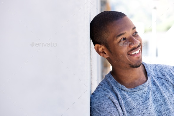happy black guy leaning against wall - Stock Photo - Images