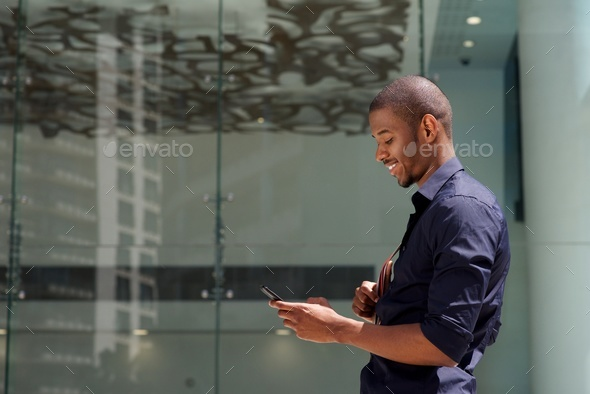 smiling black man walking outside with cellphone - Stock Photo - Images