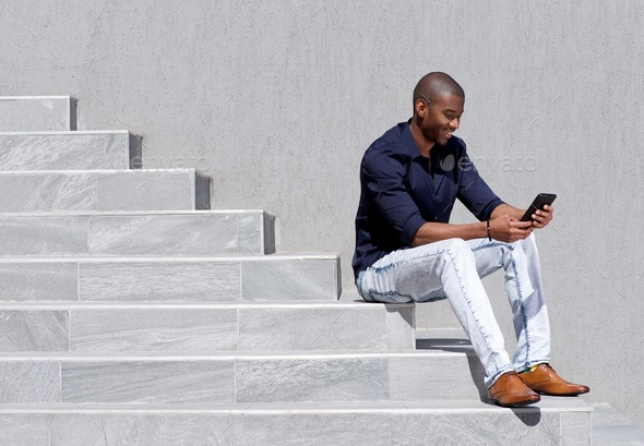young african american man sitting on steps using tablet - Stock Photo - Images