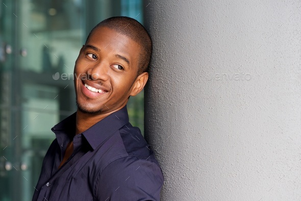 smiling black man leaning against wall outside - Stock Photo - Images