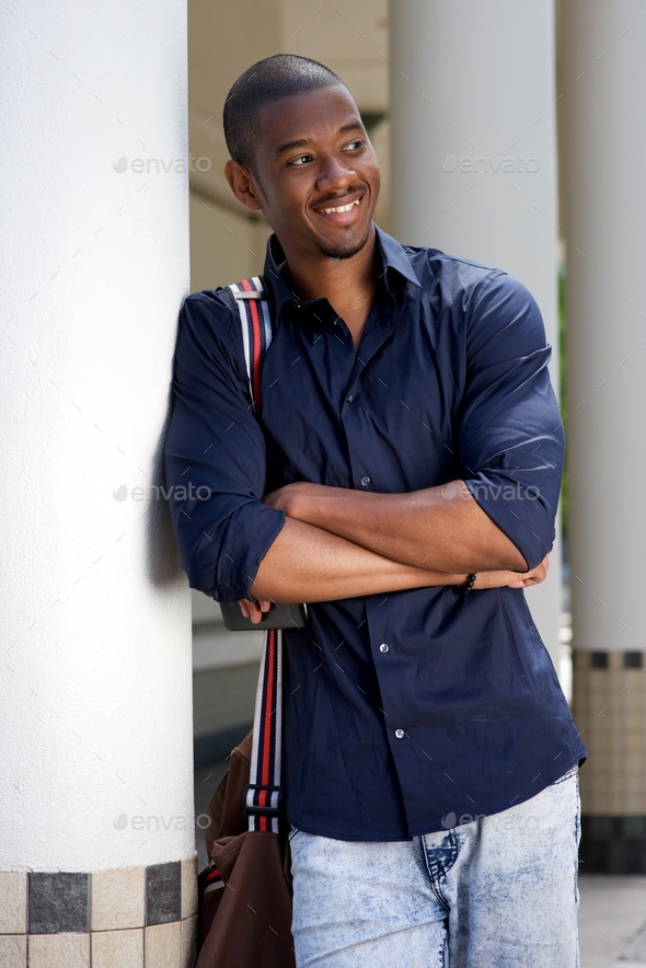 smiling young black man with bag leaning against wall - Stock Photo - Images