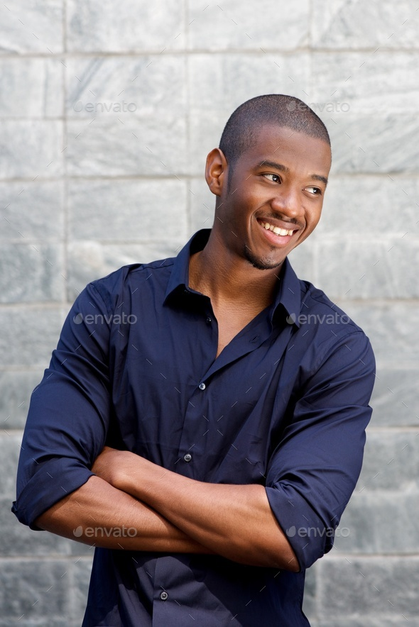 smiling young black man with arms crossed - Stock Photo - Images