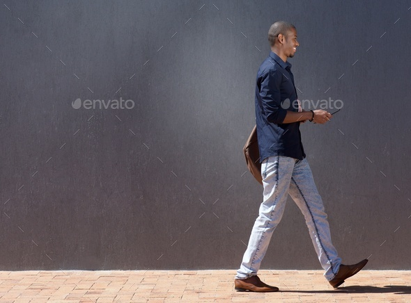black male student walking with tablet - Stock Photo - Images