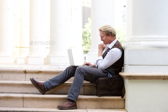 man sitting outdoors on steps and working on laptop - Stock Photo - Images