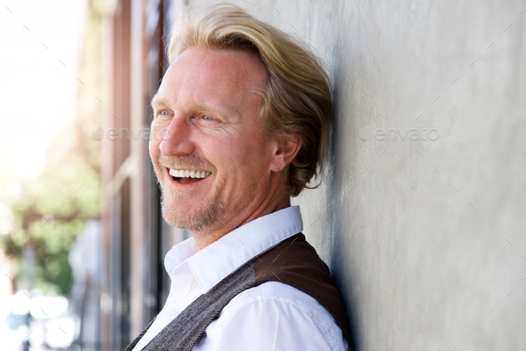 Middle aged caucasian man leaning to wall and laughing - Stock Photo - Images