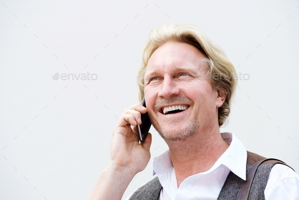 middle aged man talking on mobile phone against white wall - Stock Photo - Images