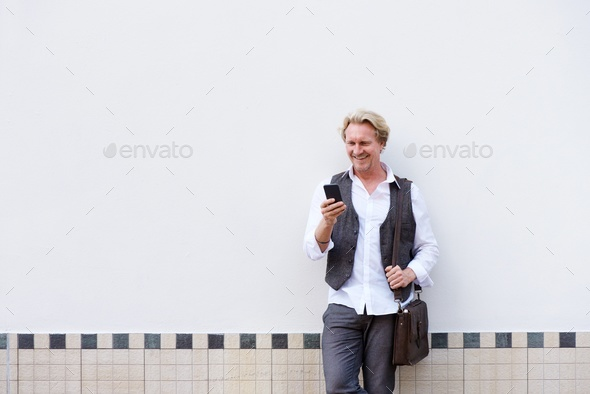 older man leaning against wall with cellphone and bag - Stock Photo - Images