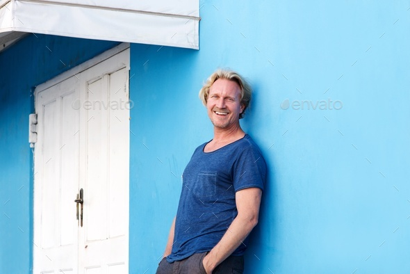 smiling middle aged man leaning against blue wall - Stock Photo - Images