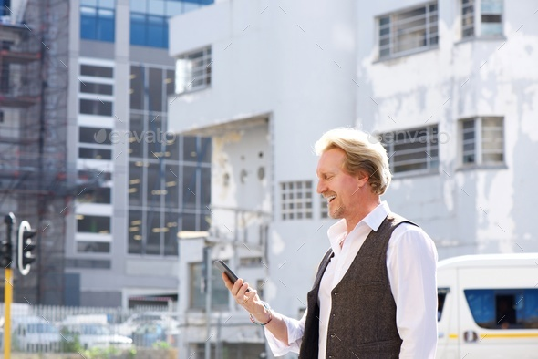 happy guy walking outdoors in the city and looking at mobile phone - Stock Photo - Images