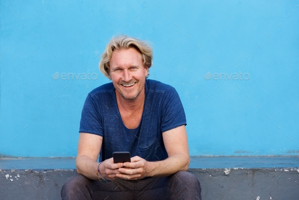 happy man sitting on steps holding mobile phone and smiling - Stock Photo - Images