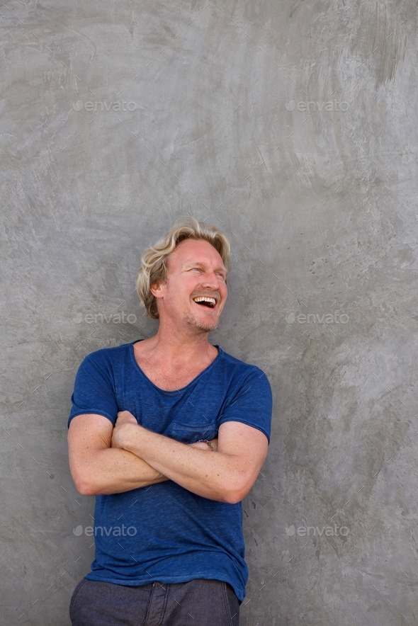 Portrait of mature man standing with arms crossed - Stock Photo - Images