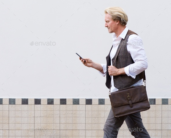 man walking outdoors and looking at mobile phone - Stock Photo - Images