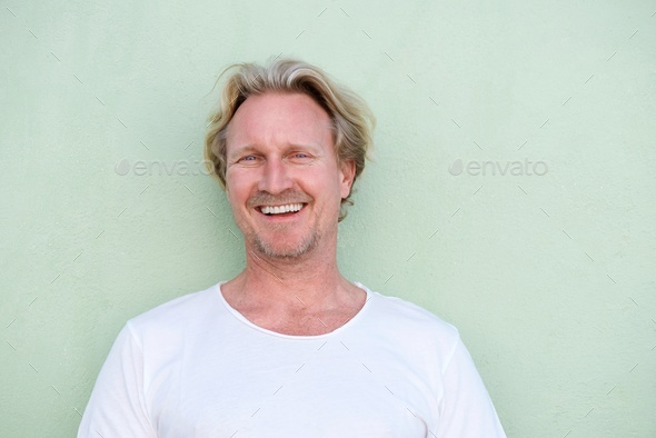 smiling middle aged man standing against green background - Stock Photo - Images