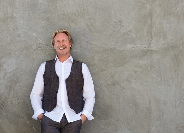 happy man smiling with hands in pocket against a wall - Stock Photo - Images