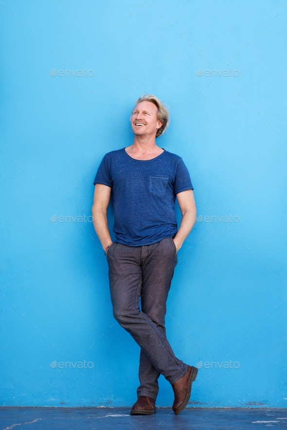 Full length man smiling against blue wall and looking away - Stock Photo - Images