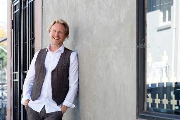 cheerful man leaning against wall and smiling - Stock Photo - Images