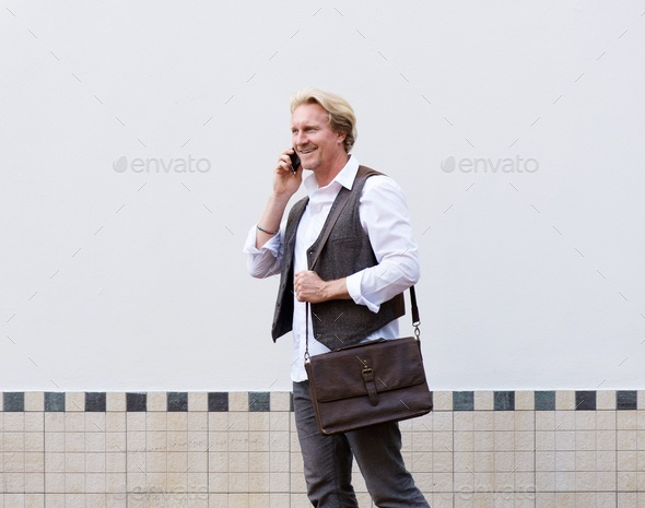 business man walking and talking on cellphone - Stock Photo - Images
