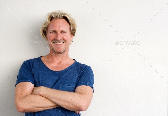 happy middle aged man posing with arms crossed against white background - Stock Photo - Images