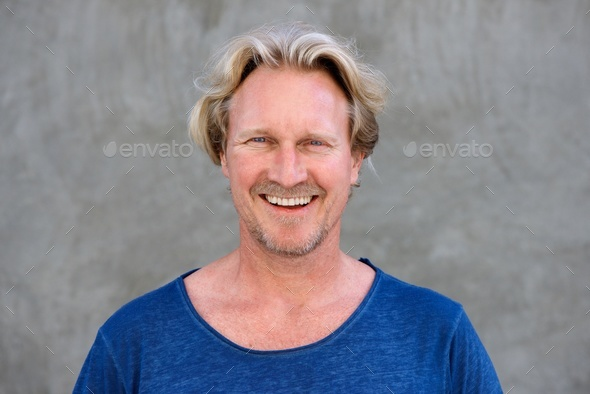 handsome older man smiling against wall - Stock Photo - Images