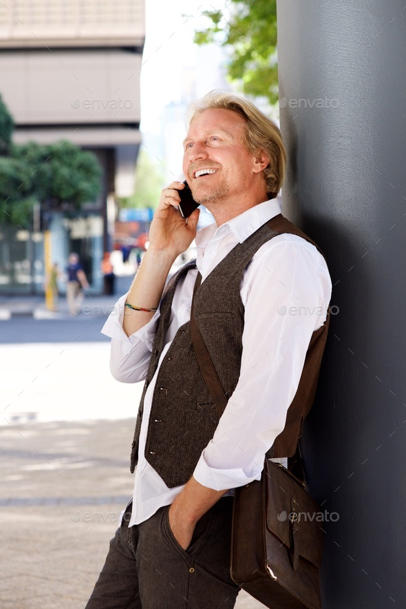 happy man leaning on wall outdoors using phone - Stock Photo - Images