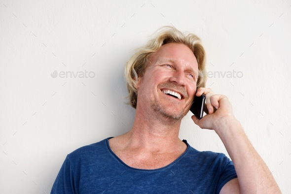 smiling man by white wall and making phone call - Stock Photo - Images