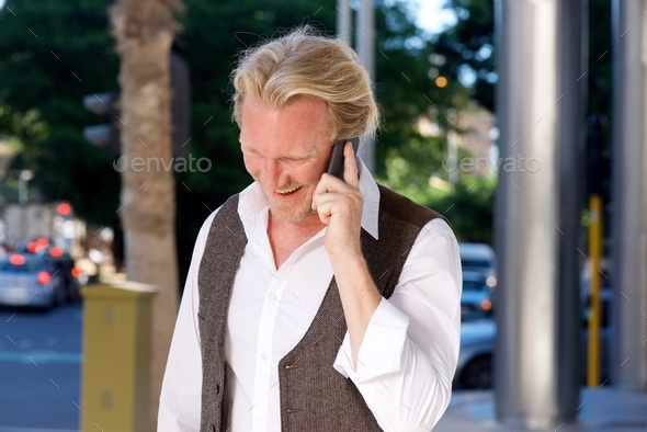 smiling caucasian man on the city street talking on mobile phone - Stock Photo - Images