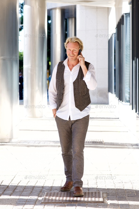 man walking around the city and talking on the mobile phone - Stock Photo - Images
