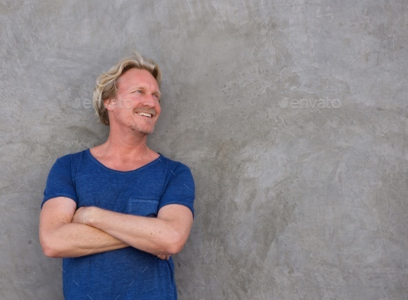 smiling man standing with arms crossed and looking away - Stock Photo - Images