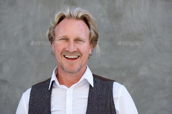 happy caucasian man standing against a wall and laughing - Stock Photo - Images