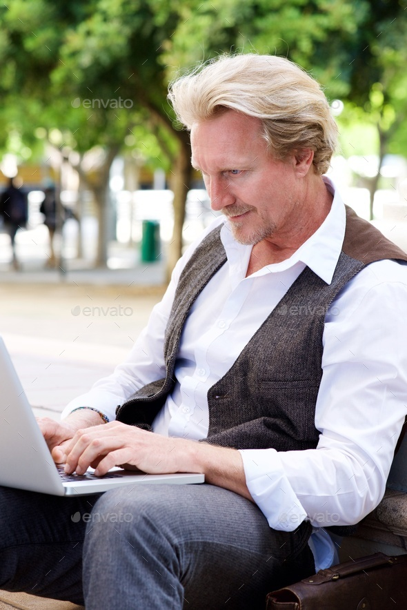 middle aged man sitting outside using laptop - Stock Photo - Images