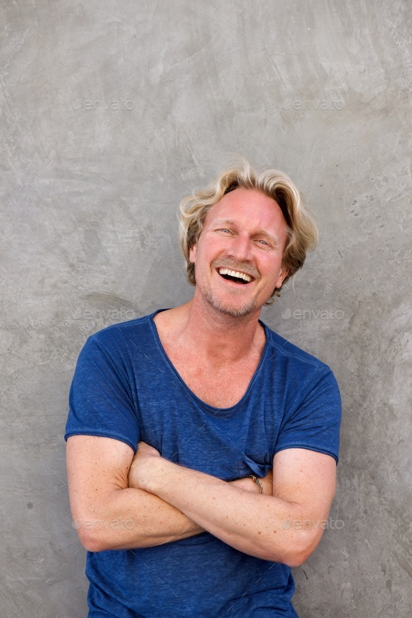 handsome caucasian man smiling with arms crossed against wall - Stock Photo - Images