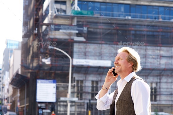 happy guy walking in the city and talking on mobile phone - Stock Photo - Images