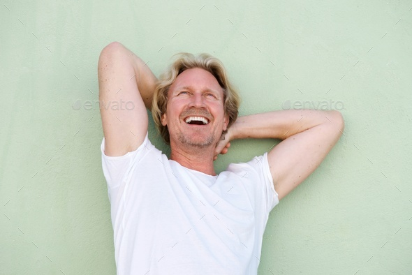 middle aged guy laughing with hands behind head - Stock Photo - Images