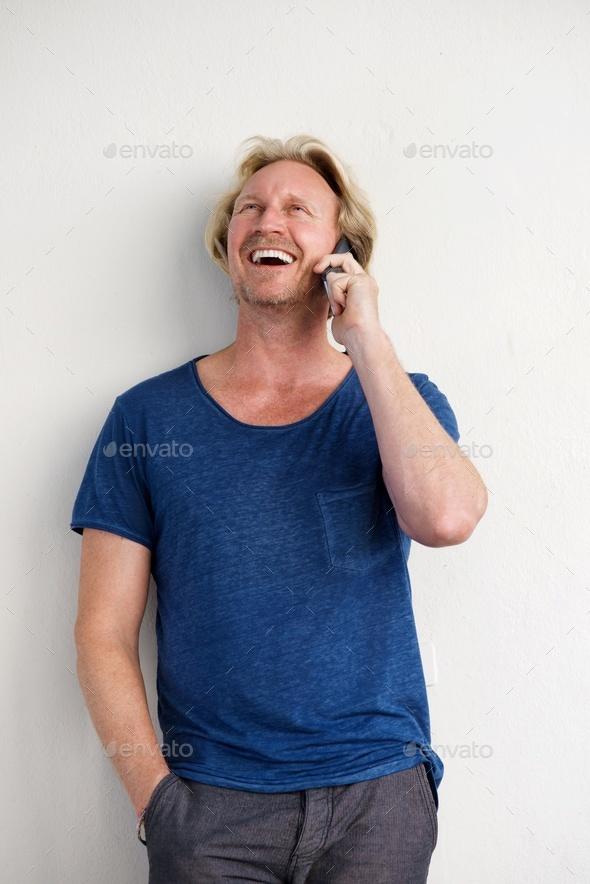happy man standing by a wall and talking on mobile phone - Stock Photo - Images