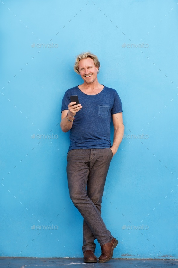 Full body happy man standing by wall with mobile phone - Stock Photo - Images