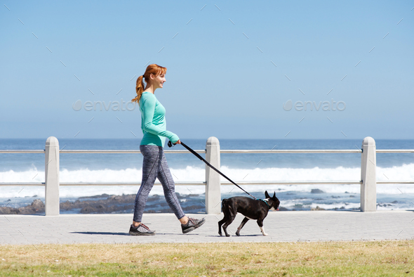 fit woman smiling and walking dog on path by sea - Stock Photo - Images