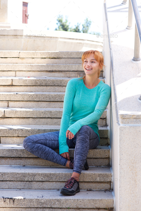 smiling female athlete resting on steps outside - Stock Photo - Images