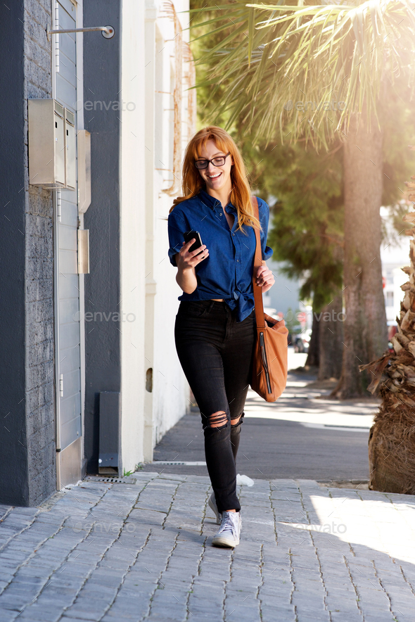 cheerful woman walking on street with smart phone - Stock Photo - Images
