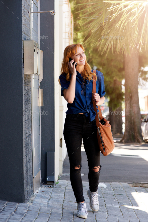smiling young woman talking on mobile phone with purse - Stock Photo - Images
