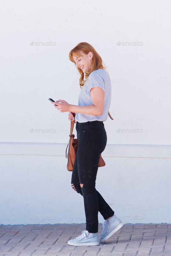portrait of smiling woman walking with mobile phone - Stock Photo - Images