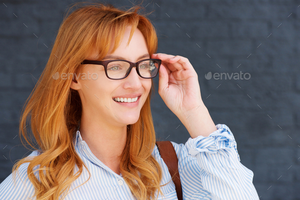 happy business casual woman with hand to glasses - Stock Photo - Images