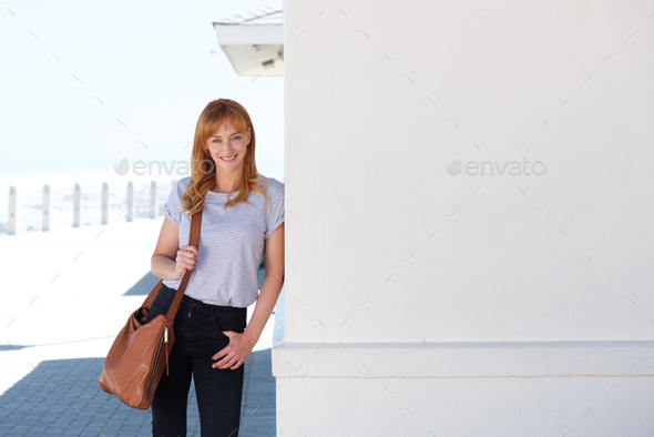happy young woman standing outside leaning on wall - Stock Photo - Images