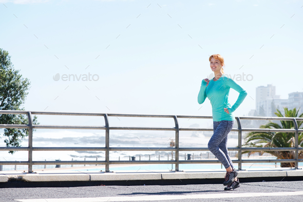 smiling female running on path outside by the sea - Stock Photo - Images