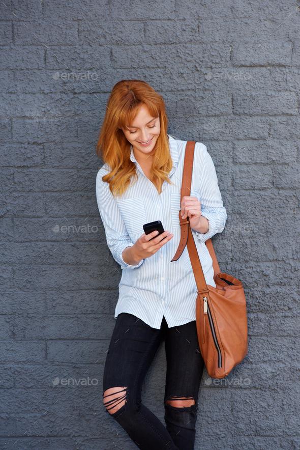 attractive young woman standing with mobile phone - Stock Photo - Images
