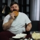 Fat Man Looks at the TV-set Drinking Beer and Eating a Burger - VideoHive Item for Sale
