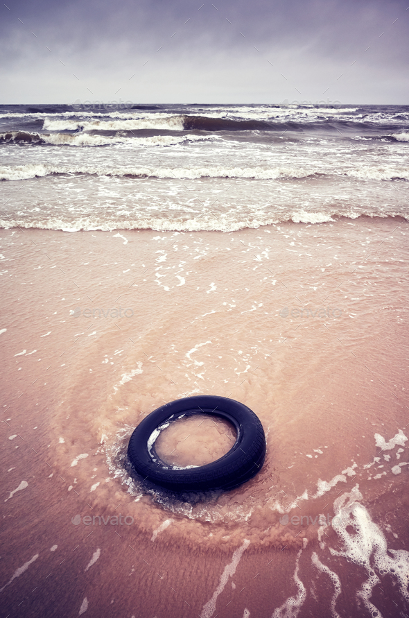 Old black rubber tire left on a beach. - Stock Photo - Images